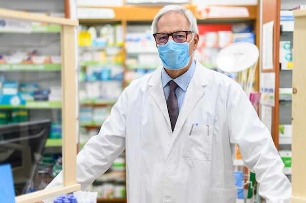Farmacista senior che indossa una maschera protettiva nel suo negozio, concetto di coronavirus
