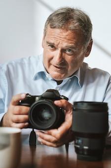 Fotografo senior che utilizza una fotocamera in uno studio