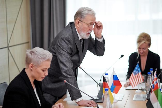 Il politico senior offre il suo piano d'azione e condivide l'opinione, uomo anziano vestito a parlare con un gruppo multietnico di partner seduti alla scrivania in sala riunioni, discutendo