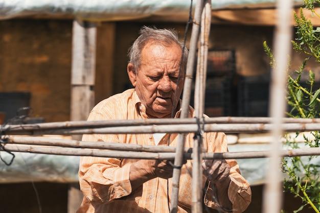 Senior che prepara i materiali per costruire la struttura in fattoria