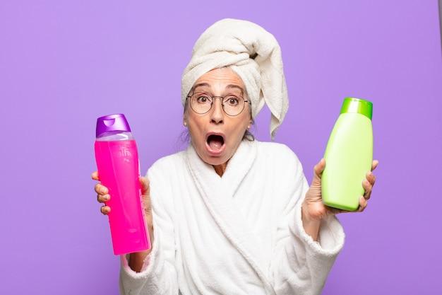 Senior bella donna dopo la doccia indossando accappatoio. concetto di prodotti per la pulizia del viso o per la doccia