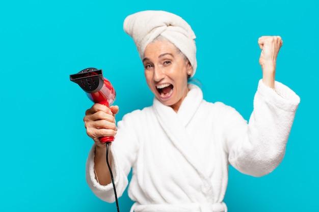 Senior bella donna dopo la doccia indossando accappatoio. concetto di asciugacapelli