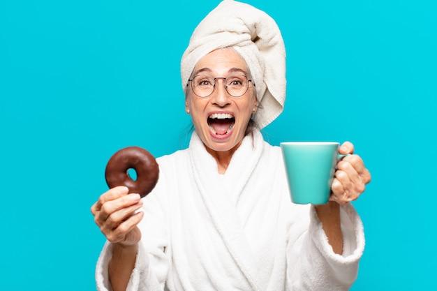 Senior bella donna dopo la doccia e indossare accappatoio e fare colazione con caffè e ciambella