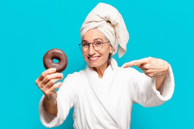 Senior bella donna dopo la doccia e indossare accappatoio e fare colazione con una ciambella