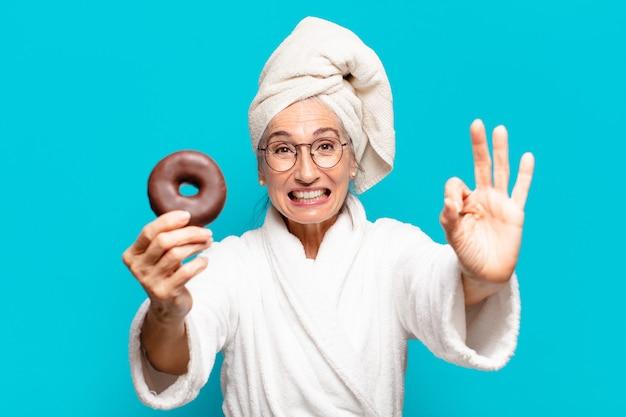 Senior bella donna dopo la doccia e indossando accappatoio e facendo colazione con una ciambella