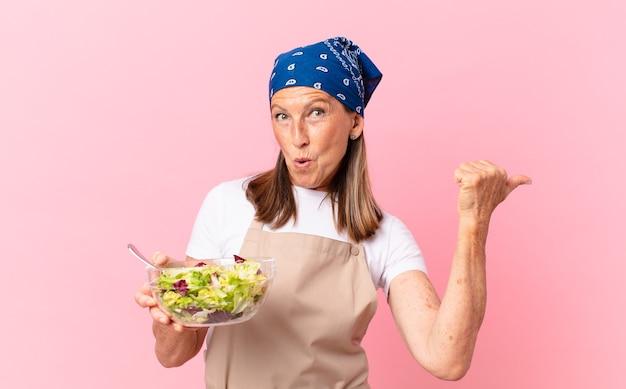 Donna graziosa anziana che prepara un'insalata