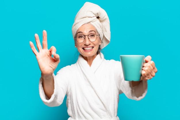 Senior bella donna che indossa accappatoio e un caffè
