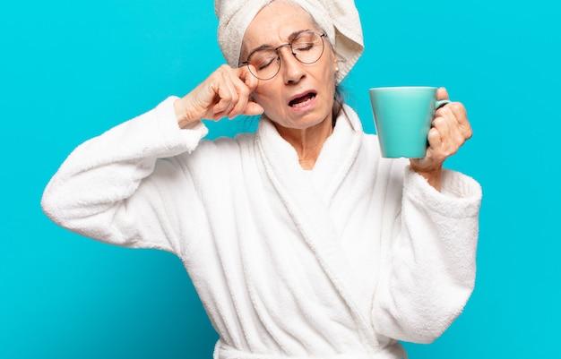 Senior bella donna che indossa accappatoio e bevendo un caffè