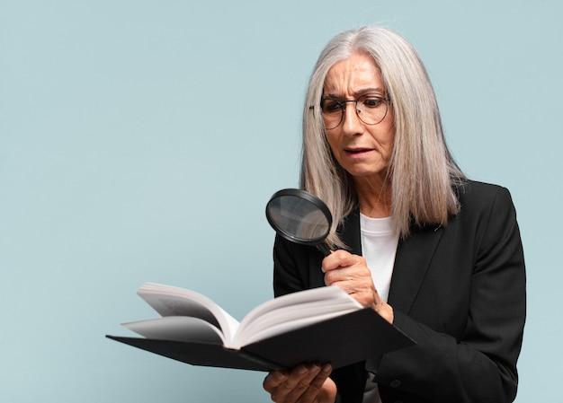 Senior bella donna con un libro e una lente d'ingrandimento. concetto di ricerca