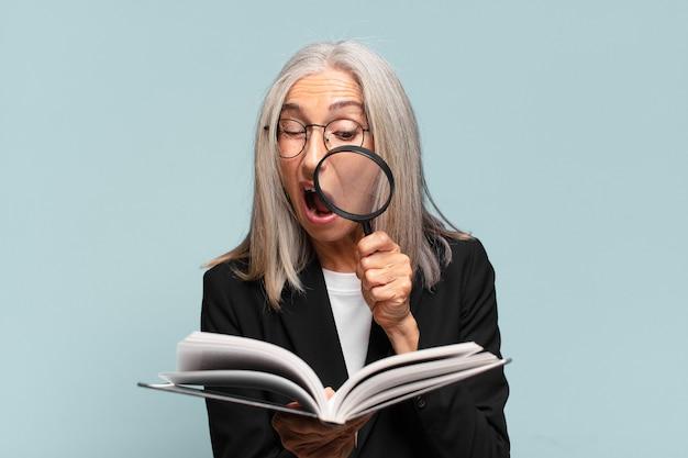 Senior bella donna con un libro e una lente d'ingrandimento.