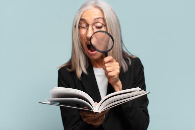 Donna graziosa anziana con un libro e una lente d'ingrandimento