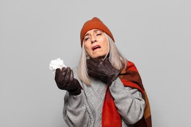 Senior bella donna con una compressa di pillole che indossa abiti invernali. concetto di influenza