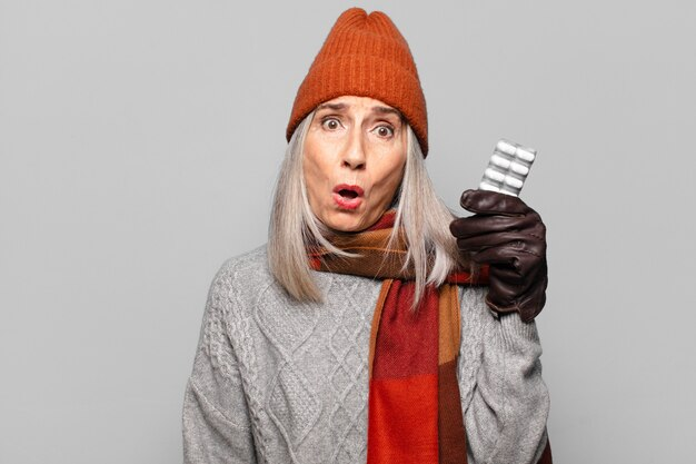 Senior bella donna con una tavoletta di pillole che indossa abiti invernali. concetto di influenza