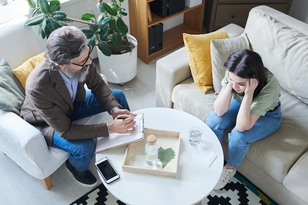 Psicologo professionista senior con la penna sopra la carta che si siede in poltrona dal tavolo davanti al paziente femminile giovane turbato sul divano