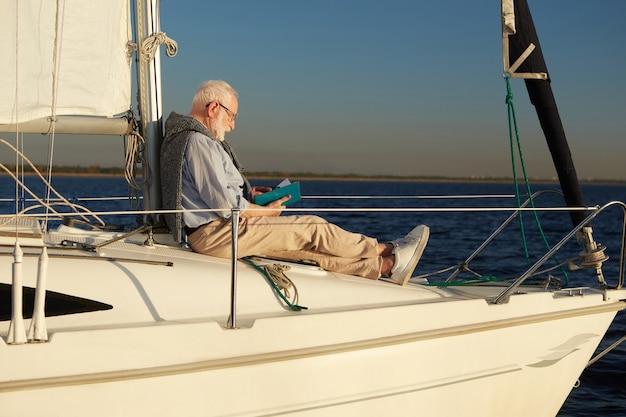 Uomo anziano rilassato che legge un libro mentre è seduto sul lato della barca a vela o del ponte di uno yacht che galleggia nel