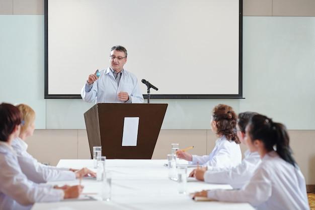 Ricercatore senior che parla alla conferenza per gli operatori sanitari e mostra una fiala del nuovo vaccino su cui la sua squadra stava lavorando