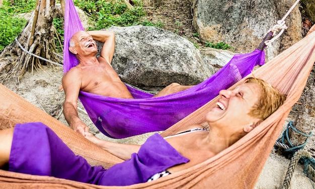 Coppia di pensionati senior vacanziere rilassante sull'amaca in spiaggia - concetto di viaggio attivo giovane anziano e felice in giro per il mondo esplorando le bellezze della natura della thailandia