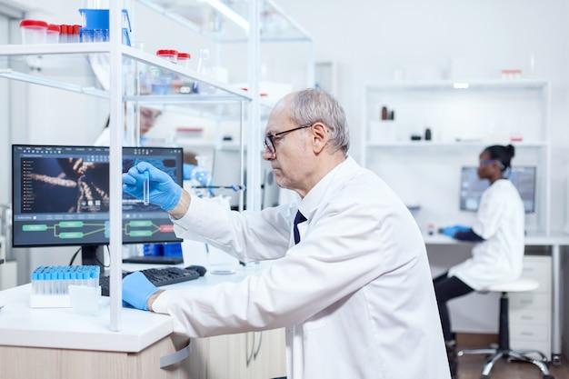 Scienziato senior e assistente africano che lavorano insieme in un moderno laboratorio. ricercatore viorolog in un laboratorio professionale che lavora per scoprire cure mediche.
