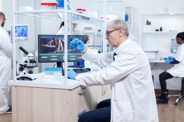 Scienziato senior che analizza e tiene in mano una provetta di microbiologia in un laboratorio occupato. ricercatore viorolog in un laboratorio professionale che lavora per scoprire cure mediche.