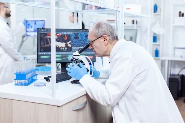 Scienziato senior che prepara e analizza i vetrini del microscopio con i colleghi impegnati. ricercatore chimico in laboratorio sterile che fa esperimenti per l'industria medica utilizzando la tecnologia moderna.