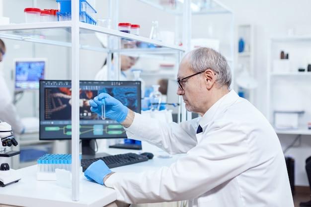 Scienziato senior che indossa guanti protettivi che tengono la provetta in laboratorio occupato. ricercatore viorolog in un laboratorio professionale che lavora per scoprire cure mediche.