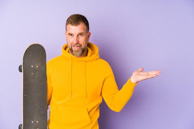 Uomo anziano del pattinatore isolato sullo spazio viola che mostra uno spazio della copia su una palma e che tiene un'altra mano sulla vita.