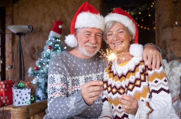 Coppia sorridente senior in cappelli di babbo natale che si abbracciano a casa nel periodo natalizio con stelle filanti. albero di natale, regali e decorazioni sullo sfondo