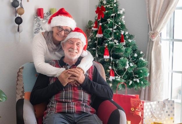 Coppia senior sorridente di due nonni con cappelli di babbo natale in attesa della famiglia - buon natale a casa per due anziani pensionati che si godono le vacanze
