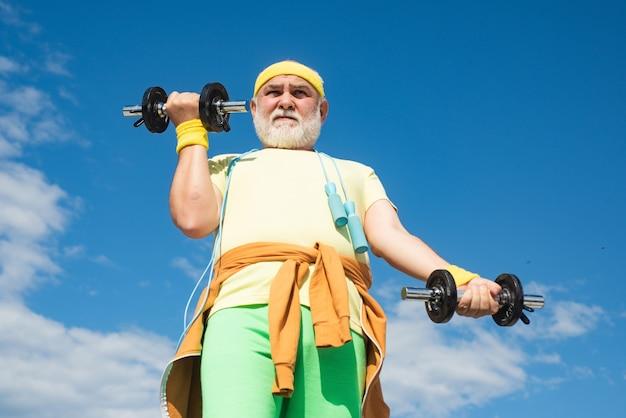 Allenamento uomo anziano con manubri di sollevamento sportivo anziano