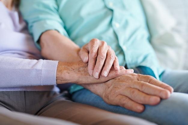 Coniugi anziani in abbigliamento casual che si tengono per mano seduti uno accanto all'altro e trascorrono del tempo davanti al televisore