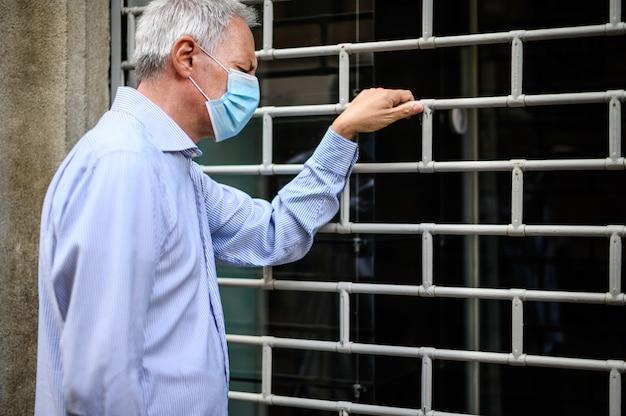 Storekeepr senior che indossa una maschera e che si rattrista davanti al suo negozio chiuso
