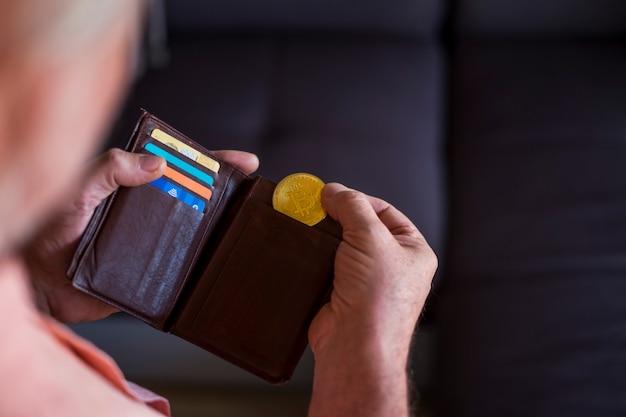 Senior prendendo un bitcoin d'oro del suo portafoglio - indoor - pagamento futuro e concetto di denaro