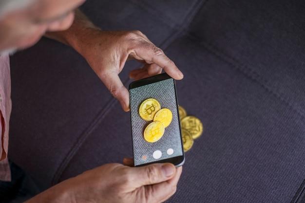 Senior che scatta una foto a tre bitcoin sul divano - denaro futuro e contanti e metodo di pagamento - foto di bitcoin - in pensione