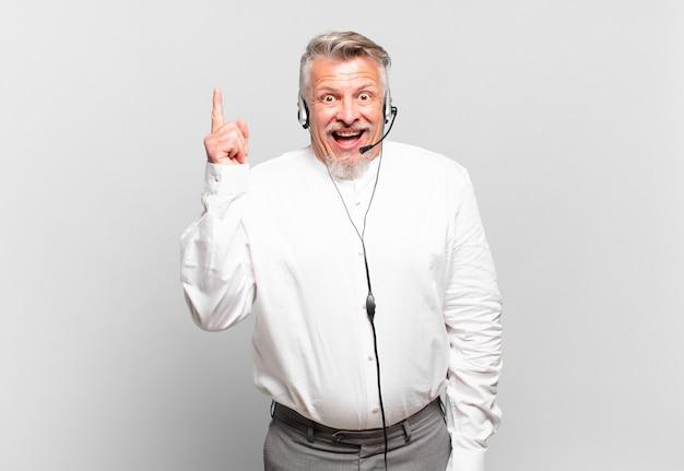 Telemarketer senior che si sente un genio felice ed eccitato dopo aver realizzato un'idea, alzando allegramente il dito, eureka!