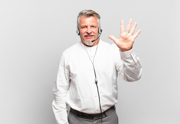 Telemarketer senior che sorride e sembra amichevole, mostra il numero cinque o il quinto con la mano in avanti, conto alla rovescia