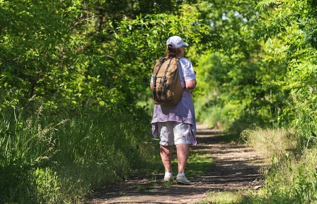 Senior donna turistica su uno sfondo di foresta. stile di vita sano escursionismo.