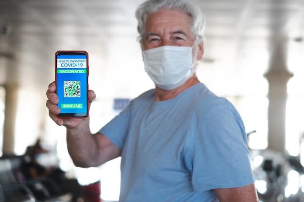 Viaggiatore anziano in aeroporto che mostra il passaporto verde sul telefono cellulare in attesa della partenza