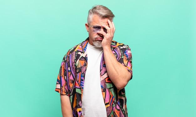 Turista viaggiatore anziano che si sente annoiato, frustrato e assonnato dopo un compito noioso e noioso che tiene il viso con la mano