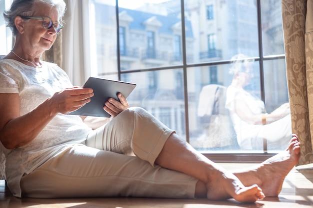 Senior viaggiatore donna nella camera d'albergo seduta sul pavimento consultando il suo tablet digitale