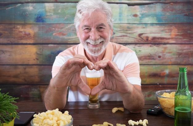 L'uomo anziano dai capelli bianchi seduto al tavolo di legno con birra e patatine fa la forma del cuore con le mani