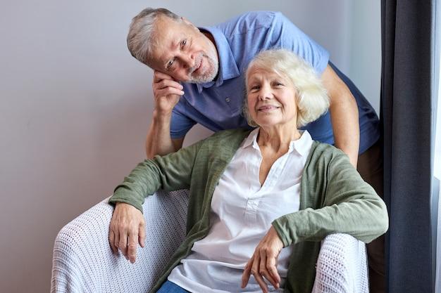 Moglie e marito senior in posa sorridente sul divano accogliente a casa, donna seduta mentre suo marito sta dietro di lei. ritratto