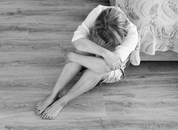 Senior donna dipendente e alcolismo da solo depressione stress seduto sul pavimento con la testa tra le mani. mal di testa, vertigini, emicrania. concetti di documentario sociale in bianco e nero