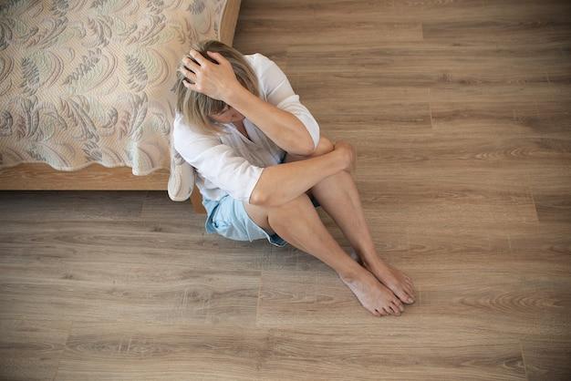 Senior donna dipendente e alcolismo da solo depressione stress seduto sul pavimento con la testa tra le mani. mal di testa, vertigini, emicrania. concetti di documentario sociale