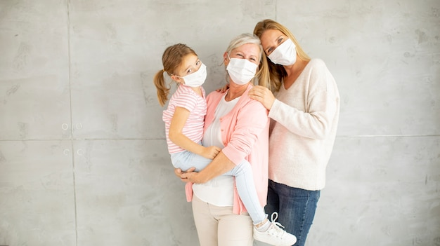 Donna senior, donna adulta e bambina carina, tre generazioni con maschere facciali protettive a casa