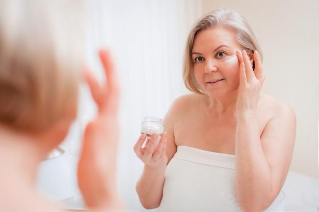 Donna senior che applica crema sul suo fronte