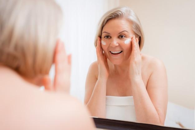 Donna senior che applica crema per il viso