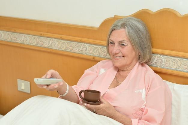 Senior donna in camera da letto con una tazza di caffè