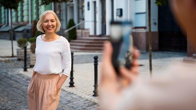 Senior donna fotografata dal partner con lo smartphone all'aperto