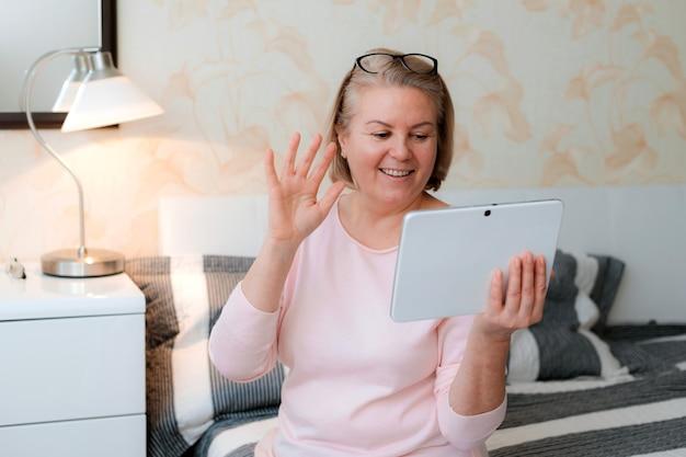 Senior donna in abbigliamento casual guardando la tavoletta digitale e sorridendo alla sua famiglia di amici e agita la mano mentre è seduto a casa