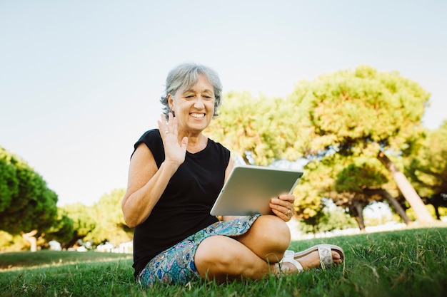 Senior donna in chat on-line con il suo tablet in un parco